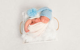 Infant in a blue hat resting Stock Image