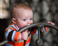 Infant Boy Blue Eyes Biting Wrought Iron Headboard Stock Photos