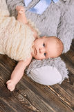 Infant boy, dark wooden background. Kid wrapped in a shawl Royalty Free Stock Photography