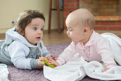 Infant boy and girl on the floor Royalty Free Stock Photo