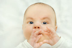 Infant boy looks into the camera camouflage, hands Royalty Free Stock Photos