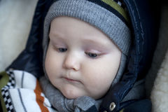Infant boy is lying in a stroller in winter clothes Royalty Free Stock Images