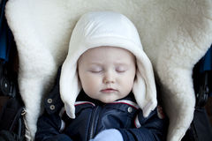 Infant boy is lying in a stroller in winter clothes Stock Photo