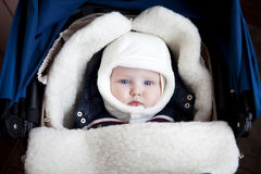 Infant boy is lying in a stroller in winter clothes Stock Photography