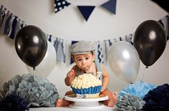 Infant boy`s first birthday cake smash Adorable baby smashing cake.  royalty free stock images