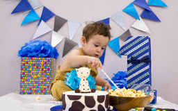 Infant boy`s first birthday cake smash Adorable baby smashing. Infant boy`s first birthday cake smash Adorable smashing cake Stock Photography