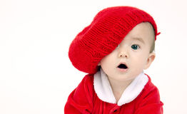 Infant Boy Sits lOOKING under his red hat. Cute Infant Boy in a horizontal composition crawling in red outfit and hat Royalty Free Stock Photos