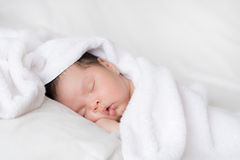 Infant boy sleeping on white bed. A 1 month old mixed race boy sleeps on white bed sheets Stock Image