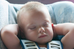 Infant boy sleeps peacefully secured with seat belts. While in the car Royalty Free Stock Image
