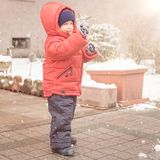 Newborn smiles cheerfully while snows. Infant boy smiles cheerfully while it`s snowing,dressed in a red winter jacket and a woolen hat Royalty Free Stock Photography