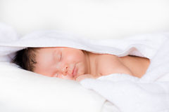 Infant boy smiles in his sleep on white bed Royalty Free Stock Photos