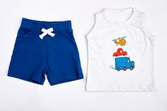 Infant boy summer shorts and y-shirt. Dark blue cotton shorts and cute white cartoon t-shirt for toddler boy. Set of natural kids clothes on white background Stock Photos