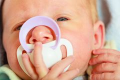 Closeup of little newborn lying with teat in mouth. Infant care, beauty of childhood concept. Little newborn baby lying calmly in bed with teat in mouth, closeup Royalty Free Stock Images