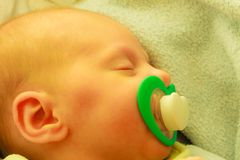 Closeup of little newborn sleeping with teat in mouth. Infant care, beauty of childhood concept. Little newborn baby sleeping calmly in bed with teat in mouth Royalty Free Stock Photography