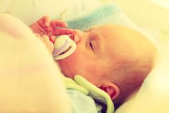 Closeup of little newborn sleeping with teat in mouth. Infant care, beauty of childhood concept. Little newborn baby sleeping calmly in bed with teat in mouth Stock Photos