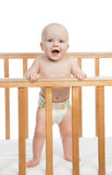 Infant child baby boy shouting in diaper in wooden bed. Infant child baby boy shouting or yelling in diaper in wooden bed on white background Royalty Free Stock Image