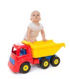 Infant child baby boy toddler with big toy car truck. Infant child baby boy toddler happy sitting with big toy car truck red yellow and blue colors in hand on a Stock Image