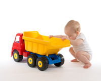 Infant child baby boy toddler big toy car truck red yellow. Infant child baby boy toddler happy sitting with big toy car truck red yellow and blue colors in hand Royalty Free Stock Photo