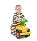Infant child baby boy toddler happy driving big toy car truck. Isolated on a white background Royalty Free Stock Photo
