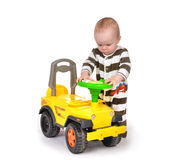 Infant child baby boy toddler happy driving big toy car truck Royalty Free Stock Image