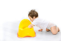 Infant child baby boy toddler play with potty toilet stool pot on a white background Royalty Free Stock Photos