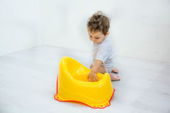 Infant child baby boy toddler play with potty toilet stool pot on a white background Royalty Free Stock Images
