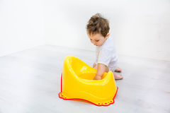 Infant child baby boy toddler play with potty toilet stool pot on a white background Stock Photo