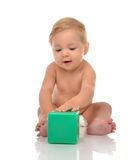 Infant child baby boy toddler playing holding green brick toy in Royalty Free Stock Images