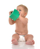 Infant child baby boy toddler playing holding green brick toy in Stock Photo