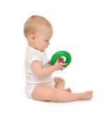 Infant child baby boy toddler playing holding green circle in ha. Nd on a floor on and looking up isolated a white background Royalty Free Stock Photography