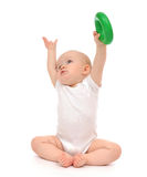 Infant child baby boy toddler playing holding green circle in ha. Nd on a floor on and looking up isolated a white background Stock Image