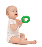 Infant child baby boy toddler playing holding green circle. In hand on a floor on and looking up isolated a white background Stock Image