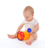 Infant child baby boy toddler playing holding watering can in ha. Nd on a floor on and looking up isolated a white background stock image