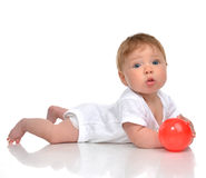 Infant child baby boy toddler playing with red ball toy in hands. On a floor on and looking at the camera isolated a white background Stock Photography