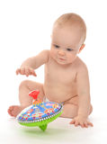 Infant child baby boy toddler playing with whirligig toy on a fl. Oor on a white background Stock Photography