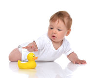 Infant child baby boy toddler playing with yellow duck toy in ha Stock Photography