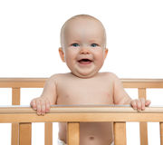 Infant child baby boy toddler shouting or yelling. In wooden bed on white background Stock Images
