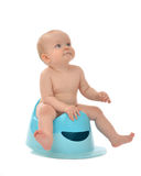 Infant child baby boy toddler sitting on potty toilet stool pot. Isolated on a white background royalty free stock images