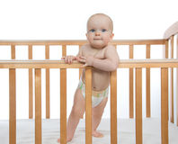 Infant child baby boy toddler  in wooden bed looking up Royalty Free Stock Images