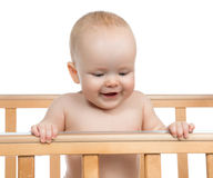 Infant child baby boy in wooden bed looking down. On white background Stock Photo