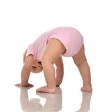 Infant child baby girl in diaper standing upside down on head in Royalty Free Stock Images