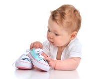 Infant child baby girl lying happy searching new shoes isolated. On a white background stock image