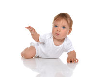 Infant child baby girl lying surprised with hand pointing Royalty Free Stock Photos