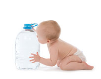 Infant child baby girl sitting with big bottle of drinking water. In diaper and give five open hand sign smiling on white background Royalty Free Stock Image