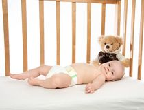 Infant child baby girl toddler lying in bed in diaper with teddy bear. On white background royalty free stock photo