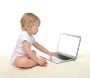 Infant child baby girl toddler sitting with computer laptop keyb Stock Photos