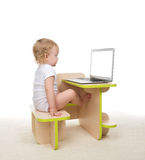 Infant child baby girl toddler sitting with hands typing on mode Stock Image