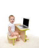 Infant child baby girl toddler sitting with modern wireless comp Royalty Free Stock Image