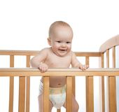 Infant child baby girl in wooden bed looking down happy smiling. On white background Stock Photography