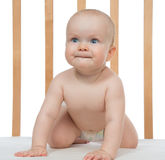 Infant child baby girl in wooden bed looking up Royalty Free Stock Photography
